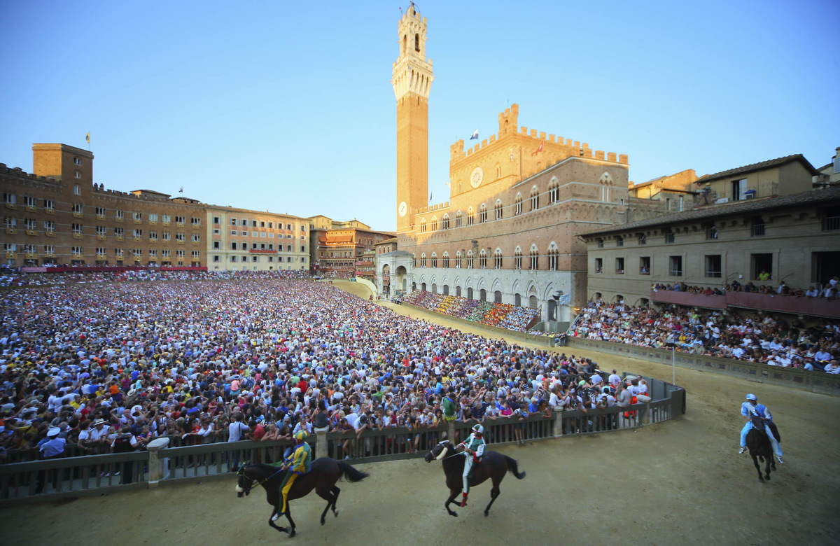 Riders take part in a practice race a day before the Palio di Siena horse race in Siena on August 15, 2013. The Palio di Siena (known locally simply as Il Palio), is a horse race held twice a year in the Tuscan city of Siena, in which jockeys ride bareback around a makeshift race course set up in the city's central square. (Fabio Muzzi/Getty Images)
