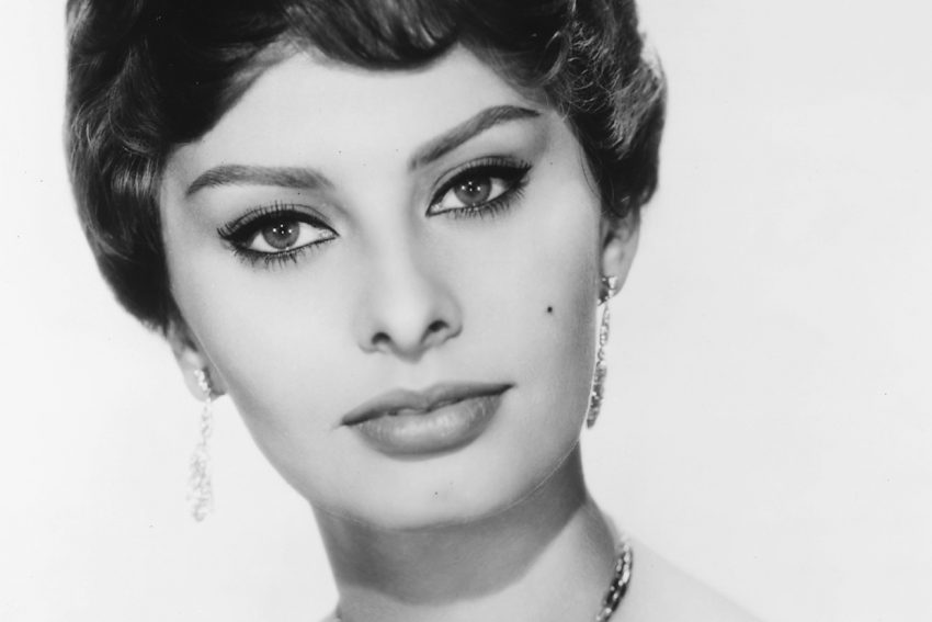 Headshot of Sophia Loren, Italian actress, looking glamorous, wearing a shoulderless dress and a diamond necklace and diamond earrings in a studio portrait, against a white background, circa 1950. (Photo by Silver Screen Collection/Getty Images)
