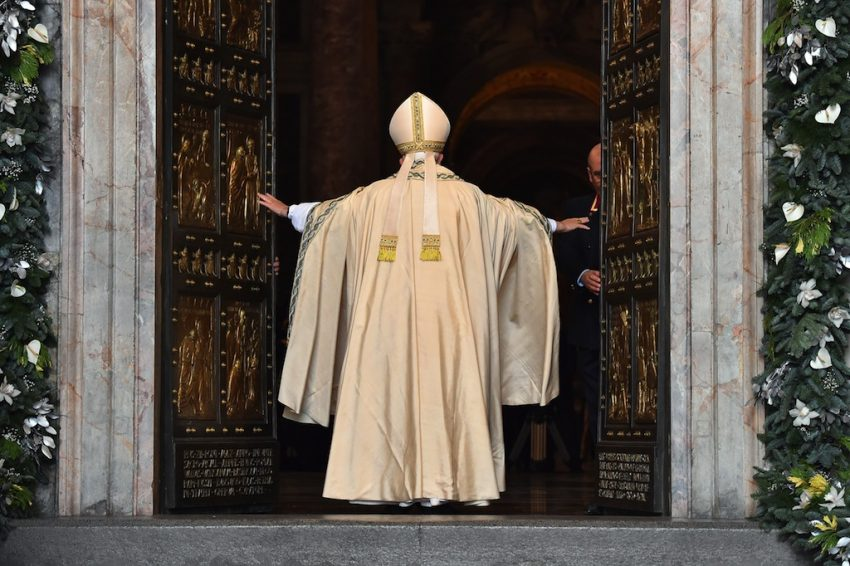 "Pope Francis opens a ""Holy Door"" at St Peter's basilica to mark the start of the Jubilee Year of Mercy, on December 8, 2015 in Vatican. In Catholic tradition, the opening of ""Holy Doors"" in Rome symbolises an invitation from the Church to believers to enter into a renewed relationship with God.   AFP PHOTO / VINCENZO PINTO / AFP / VINCENZO PINTO        (Photo credit should read VINCENZO PINTO/AFP/Getty Images)"